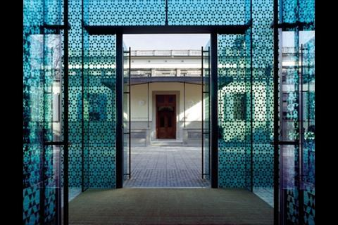 The museum's entrance pavilion stands off to one side of the Italianate villa, behind a green veil of patterned glass